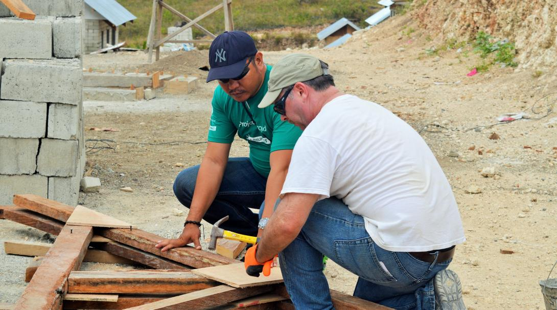 A Projects Abroad volunteer works together with a local staff member to rebuild a school as part of the disaster relief project.
